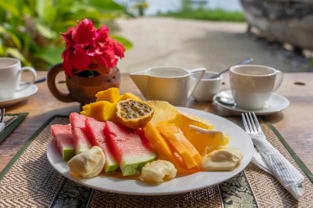 Frutti tropicali su un piatto per la colazione, primo piano. anguria fresca, banana, frutto della passione, ananas, jackfruit, mango, papaia, arancia per mangiare nel ristorante sulla spiaggia, isola di zanzibar, tanzania, africa