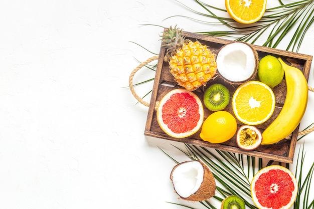 Frutti tropicali e foglie di palma su uno sfondo bianco, vista dall'alto.