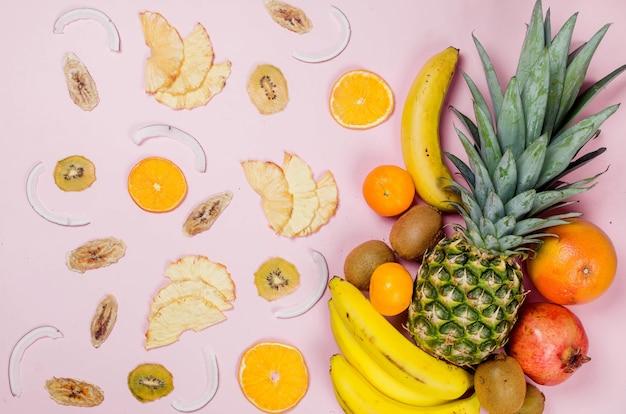 Frutti tropicali. ananas. cocco, arancia, banane e cotolette di frutta secca su sfondo rosa. concetto di cibo. composizione tropicale estiva. vista dall'alto, copia dello spazio.