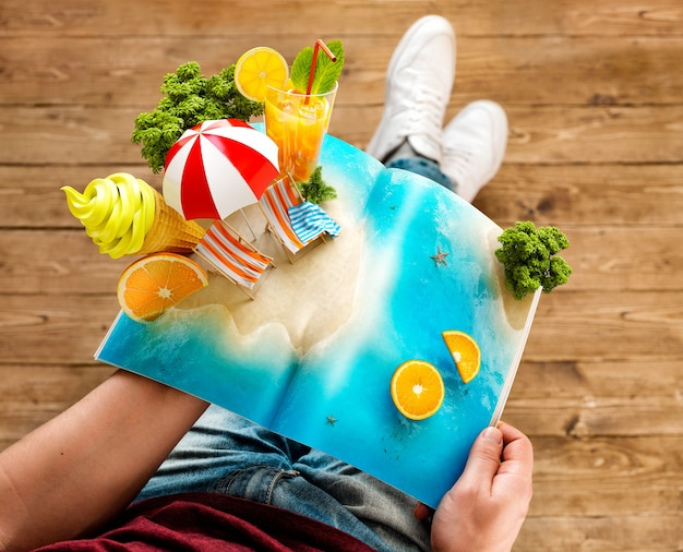 Isola tropicale con palme, gelato e succo di frutta fresco su una pagina della rivista aperta nelle mani.