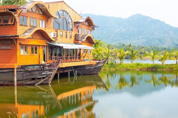 Paesaggio tropicale. casa in legno a forma di barca sull'oceano con vista sulle montagne. viaggi e turismo in asia.