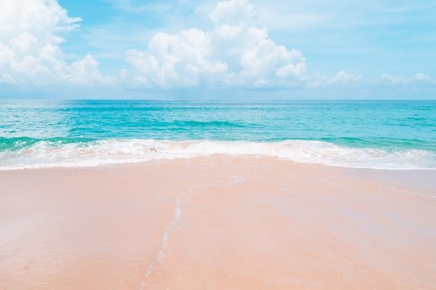 Natura tropicale spiaggia pulita e sabbia bianca in estate con cielo azzurro sole e sfondo bokeh.