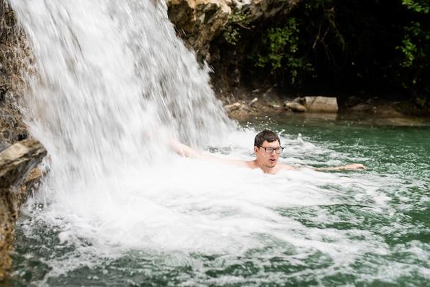 Natura tropicale e vacanza. uomo che nuota nel fiume di montagna con una cascata