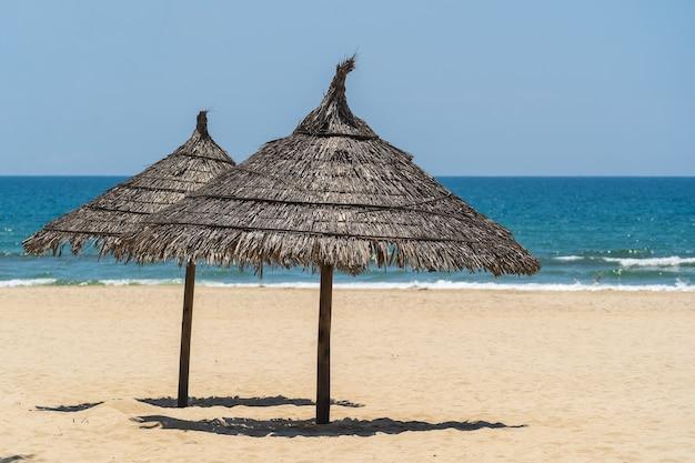 Spiaggia di sabbia tropicale e acqua di mare estiva con cielo blu e due ombrelloni di paglia nella città di danang, vietnam. concetto di viaggio e natura