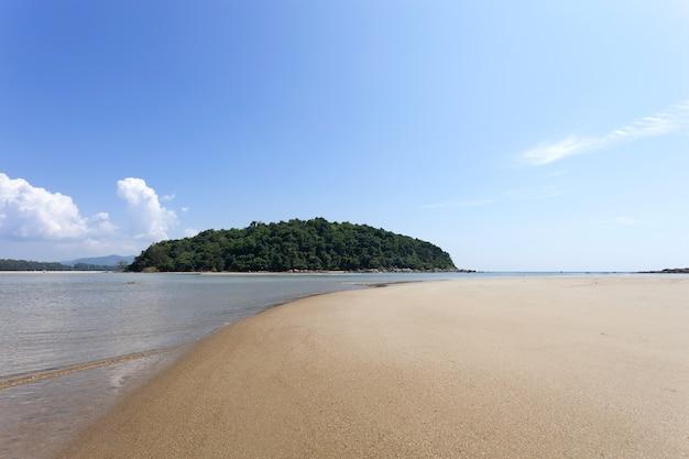 Spiaggia sabbiosa tropicale con l'oceano blu della piccola isola e il fondo del cielo blu