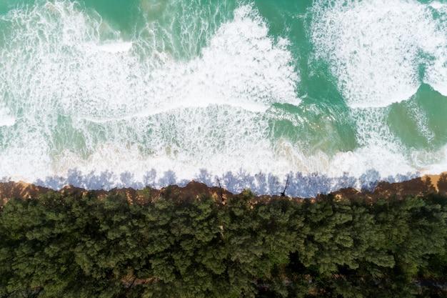 Mare tropicale con l'onda che si schianta sul colpo del fuco di vista aerea della spiaggia.