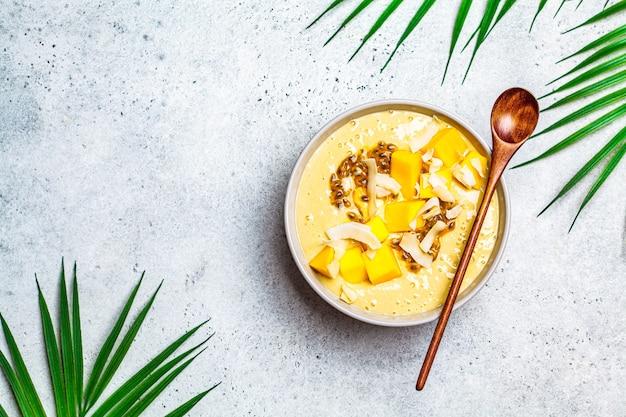 Ciotola frullato tropicale con mango, frutto della passione e cocco, sfondo chiaro.