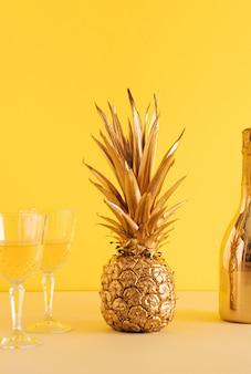 Ananas dorato estivo tropicale e bottiglia di champagne con due bicchieri di champagne su sfondo giallo illuminante. arte astratta creativa