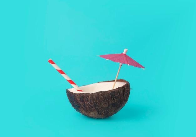 Estate tropicale e concetto minimo di vacanza. noce di cocco su uno sfondo blu con una cannuccia di cocktail. vacanza, viaggio, idea di spiaggia.