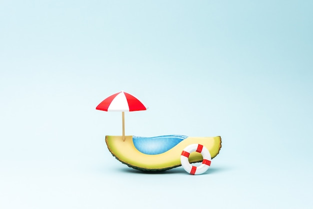 Concetto di piscina tropicale realizzata con ombrellone alla frutta di avocado e anello da nuoto