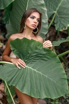 Una giovane donna tropicale copre il suo corpo con una grande foglia verde