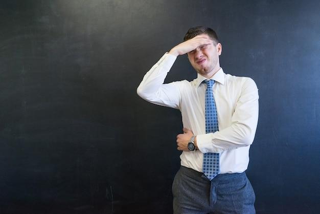 Guai imprenditore in tuta con mal di testa dopo un incontro di lavoro isolato su nero. tiene la testa con dolore. uomo d'ufficio con problemi