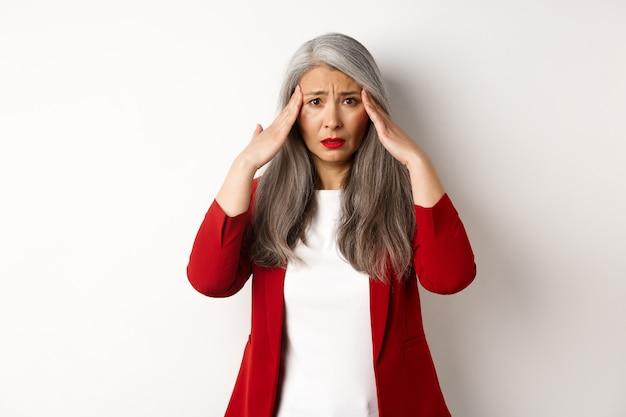 Imprenditore femminile asiatico travagliato con mal di testa, toccando la testa e accigliato, in piedi su sfondo bianco.