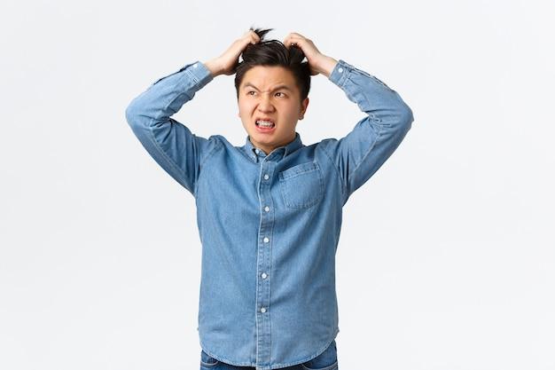 Ragazzo asiatico turbato e infastidito che sembra frustrato nell'angolo in alto a sinistra e si gratta la testa con irritazione. l'uomo interessato che pensa alla soluzione, ha un grosso problema, in piedi su uno sfondo bianco.
