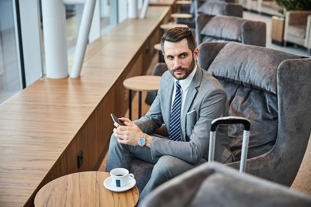 Uomo d'affari in difficoltà con uno smartphone in mano