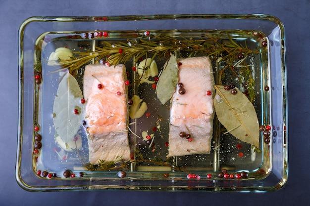Trota (salmone) sott'olio con erbe e spezie, cotta secondo il metodo confit. piatto tradizionale francese. passo dopo passo. avvicinamento.