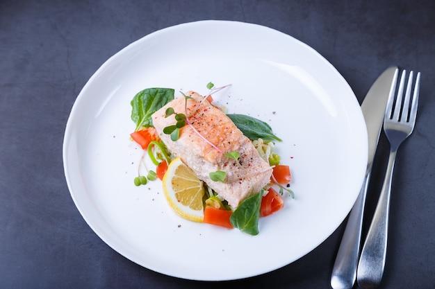 Trota (salmone) con verdure, limone e microgreens, cotta secondo il metodo confit. piatto tradizionale francese. passo dopo passo. avvicinamento.