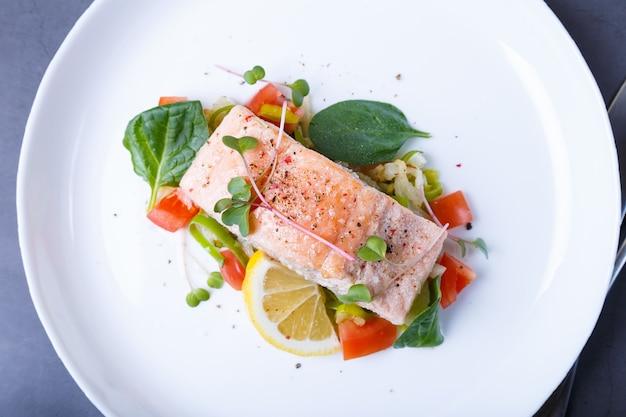 Trota (salmone) con verdure, limone e microgreens, cotta secondo il metodo confit. piatto tradizionale francese. passo dopo passo. vista dall'alto.