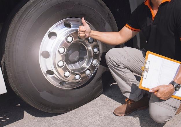Autista di camion che fa il pollice in su dopo aver controllato la sicurezza di ruote e trire di camion