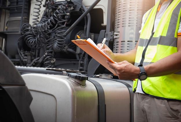 Un autista di camion che tiene appunti che controlla sicurezza un grande serbatoio di carburante di semi camion.