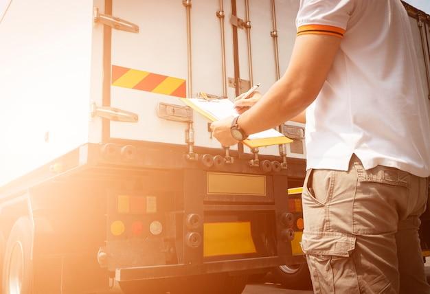 L'autista del camion sta controllando l'ispezione della lista di controllo della manutenzione di sicurezza dei camion