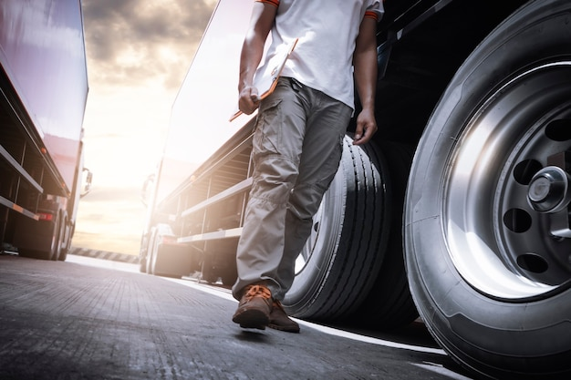 Camionista camminare e controllare un camion ispezione di ruote e pneumatici manutenzione e sicurezza camion