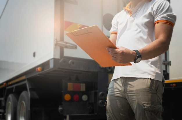 Camionista carta da lettere su appunti in piedi con camion rimorchio. manutenzione e ispezione di sicurezza del veicolo.