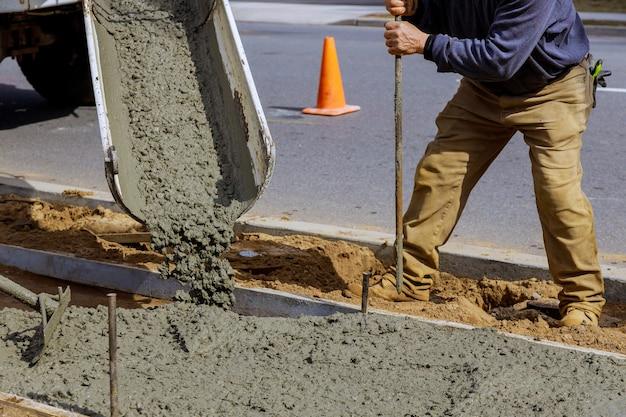 Autobetoniera versando cemento concreto in un calcestruzzo con marciapiede