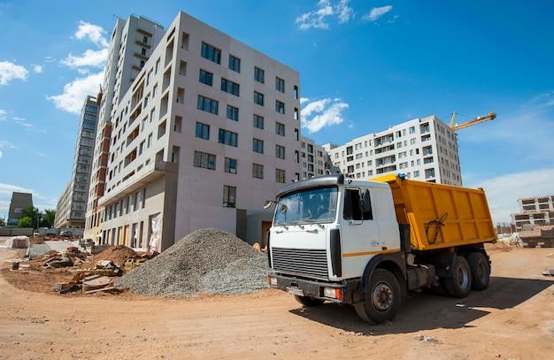 Camion cavalca in un cantiere edile sullo sfondo di una nuova casa