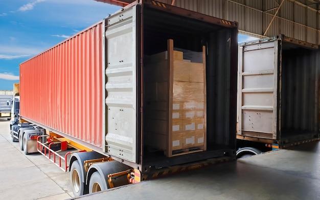 L'attracco del container del rimorchio del camion carica i pallet delle merci della spedizione al magazzino, alla logistica del settore merci e al trasporto