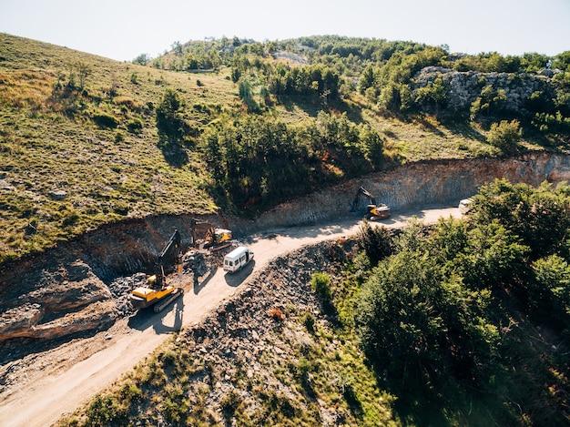 I camion guidano lungo la strada verso la cava di sabbia sullo sfondo del verde