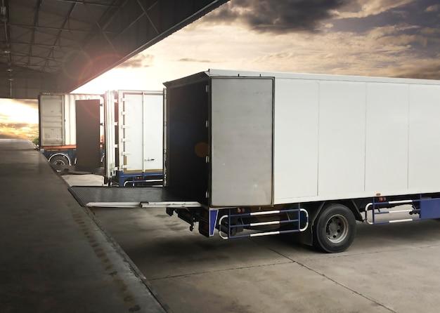 Camion parcheggiati che caricano al magazzino del bacino di spedizione di merci industria del trasporto di camion