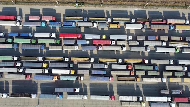 Camion nel parcheggio da una prospettiva a volo d'uccello. vista dall'alto di una coda di trasporto merci nel porto. esportazione di prodotti agricoli in europa
