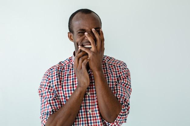 Vera emozione. allegro adulto afro americano afro americano uomo sorridente su sfondo bianco