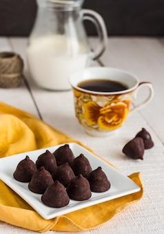 Cioccolatini al tartufo con una tazza di caffè e panna su un bianco