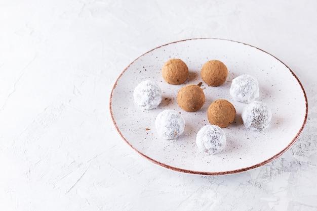 Tartufi in polvere di cacao e latte di cocco secco su un piatto