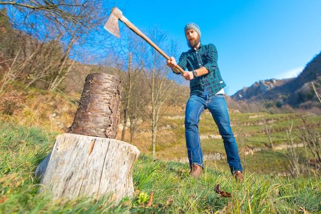 Il tronco di legno sta per essere tagliato con un ascia barbuto
