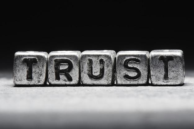 Concetto di fiducia. l'iscrizione su cubi 3d in metallo isolati su uno sfondo nero, stile grunge