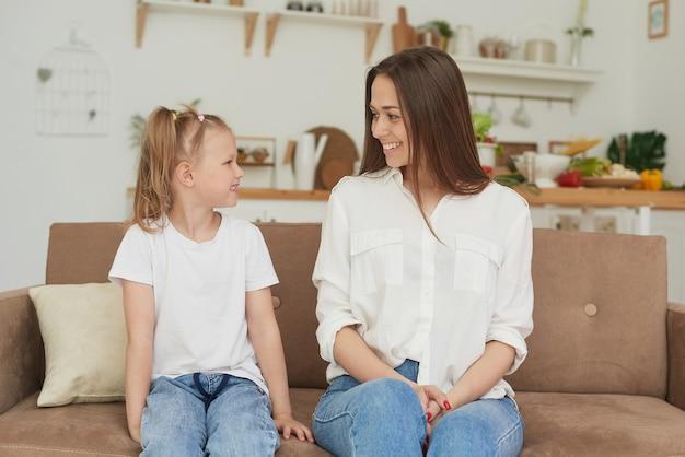 Il rapporto di fiducia tra mamma e figlia. conversazione di una donna con una bambina a casa sul divano in cucina. migliori amici buon fine settimana di maternità insieme al concetto di bambino.