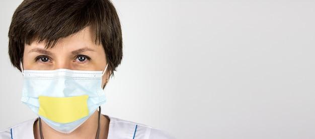 La verità sul nuovo coronavirus 2019 2019-ncov . il segreto medico concetto. medico della donna con le labbra nastrate in uniforme bianca su sfondo bianco. pandemia. panico. informazione.