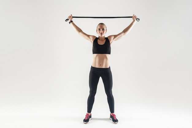Attrezzatura trx. forte donna che tiene la corda per saltare vicino alla testa e che guarda l'obbiettivo. foto in studio, sfondo grigio