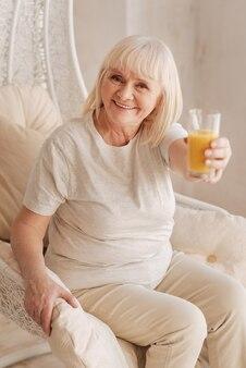 Provalo. felice donna senior positiva che tiene un bicchiere e sorride mentre ti offre succo d'arancia appena spremuto