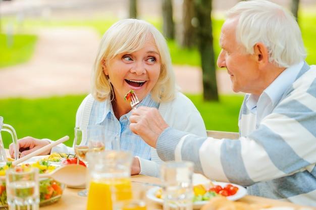 Prova il mio pasto! uomo anziano che alimenta la sua allegra moglie con insalata fresca mentre entrambi sono seduti al tavolo da pranzo all'aperto