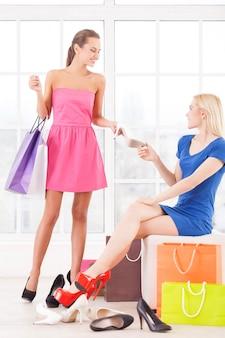 Prova queste scarpe. due giovani donne attraenti che scelgono le scarpe in un negozio di scarpe
