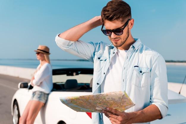 Cercando di trovare la loro strada. giovane frustrato che esamina la mappa mentre la sua ragazza si appoggia alla loro decappottabile bianca sullo sfondo