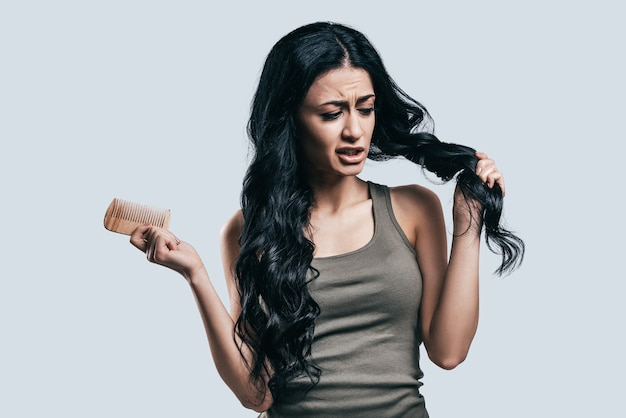 Cercando di far sembrare i suoi capelli migliori. attraente giovane donna in abbigliamento casual che si pettina i capelli con la faccia confusa mentre sta in piedi su uno sfondo grigio