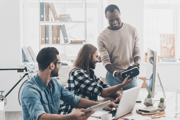 Provando una nuova tecnologia innovativa! il team di sviluppo collabora nel loro ufficio mentre un bell'uomo con i capelli lunghi dà l'auricolare vr al suo collega