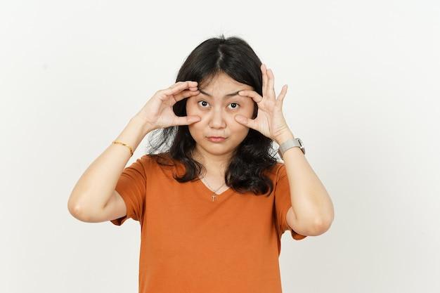 Cercando di aprire gli occhi di una bella donna asiatica che indossa una maglietta arancione isolata su sfondo bianco