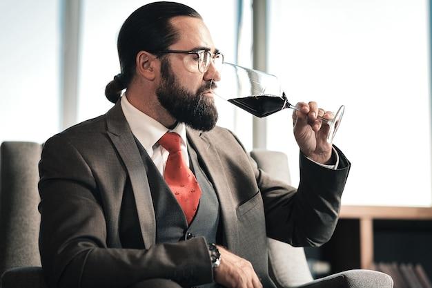 Provare il vino rosso. uomo d'affari che indossa il vino rosso seduto vicino alla finestra e cercando un gustoso vino rosso