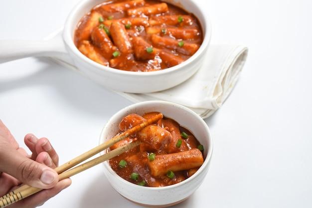 Tteokbokki o torta di riso piccante coreanal'immagine di un delizioso tteokbokki piccante su sfondo bianco